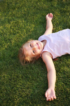 Happy cute girl relaxing on a grass field Stock Photo - 5570694
