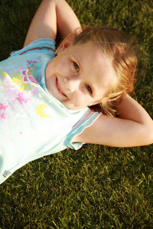 Happy cute girl relaxing on a grass field Stock Photo - 5640744