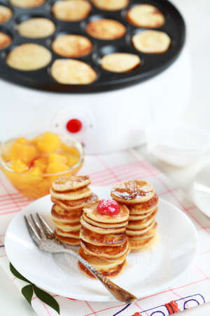 Sweet pancakes with  compote and pancake maker background photo