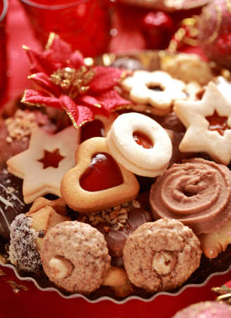 Detail of delicious Christmas cookies with candles in red tone photo