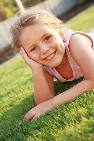 Happy cute girl relaxing on a grass field photo