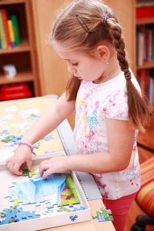 educational: Girl playing with puzzle Stock Photo