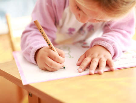 kids writing: Cute little girl painting at home