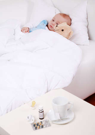 sick baby: Baby and teddybear lying in bed with cup of tea and medicine Stock Photo