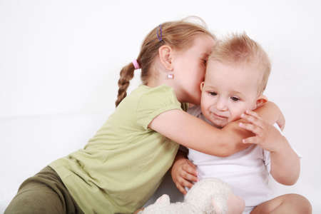 Cute older sister giving a kiss to her brother Stock Photo - 6555989