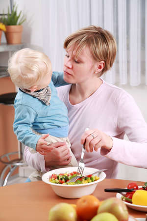 Little boy tasting vegetable salad with his mother photo
