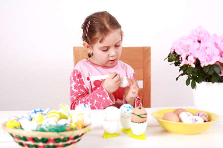 Cute little girl painting Easter eggs photo