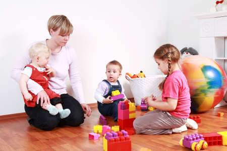baby nursery: Kids in kindergarten with their teacher Stock Photo