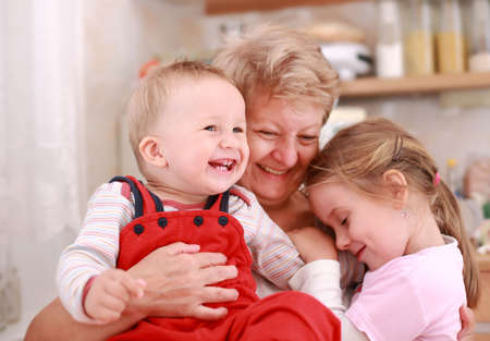 grandmother grandchild: Cute little boy and little girl happy with grandmother Stock Photo