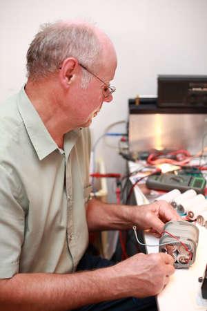 diagnosing: senior electrician working