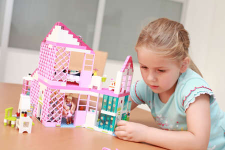 Cute little girl plays with dolls house photo