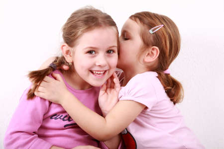 Girl whispering a secret to her girlfriend photo