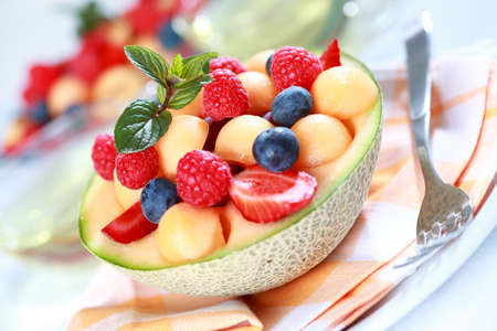 Delicious fresh fruits served in melon bowl as dessert photo