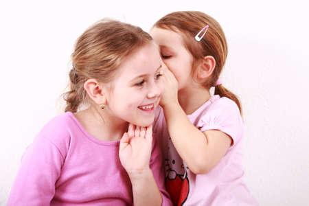 Girl whispering a secret to her girlfriend