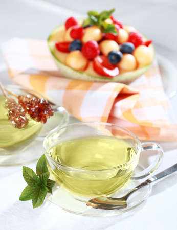 Two cups of green herbal tea with sugar stick and fresh fruits photo