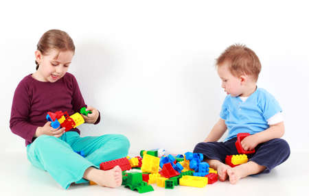 Adorable kids playing together with blocks photo