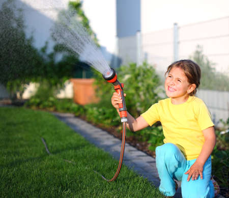 regando plantas: Ni�a de riego de la hierba en el jard�n Foto de archivo