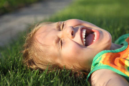 Happy cute girl laughing on a grass field Stock Photo - 7140289