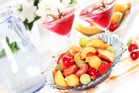 Delicious fresh fruits served in bowl  with two ice tea or cocktails photo