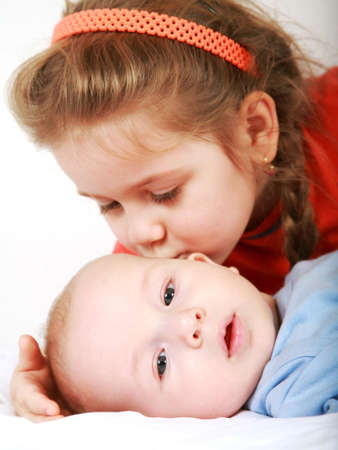 sibling: Cute older sister giving a kiss to her brother Stock Photo