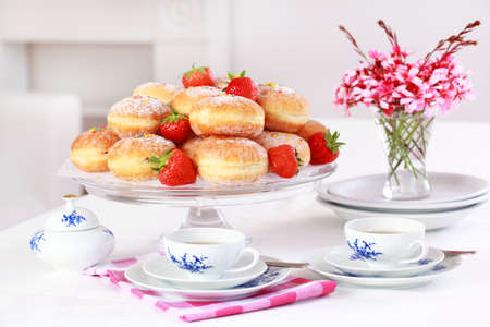 Doughnut filled with strawberry jam - German national dish with cup of tea photo