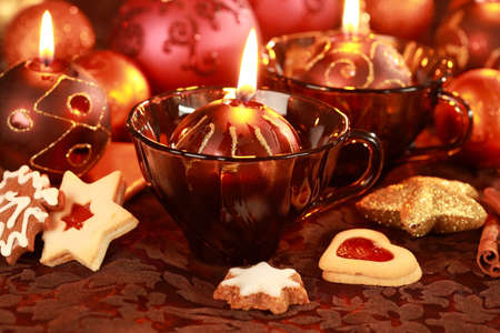 Christmas still life with candles and cookies in brown and red tone photo