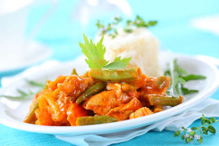 Red chicken curry stripes with rice and vegetable photo