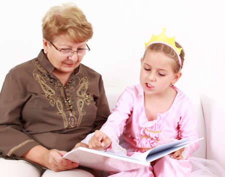 Cute little girl reading a book with her grandmother photo