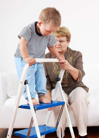 Cute little boy playing with his grandmother and training walking stairs photo