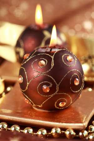 Christmas still life with candles and jingle bells in brown and golden tone photo