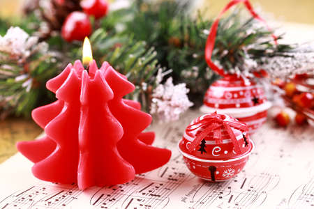 Christmas still life with candles, jingle bells and music notes photo