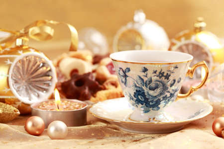 Tea for Christmas with sweet cookies with candles in golden tone