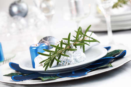 Place setting in white with rosemary for Christmas