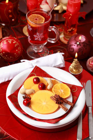 Place setting for Christmas with fresh fruits and hot wine punch photo