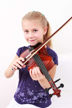 playing instrument: Cute little girl playing violin