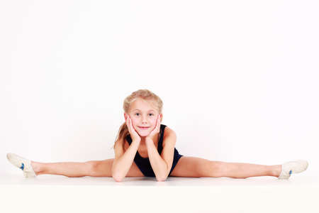 Cute little girl making splits on white background photo