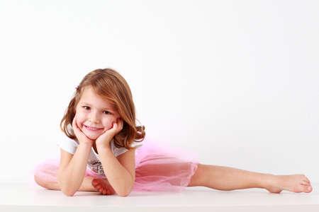 Cute little girl making splits on white background photo