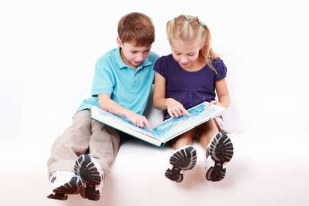 sibling: School kids reading a book  Stock Photo