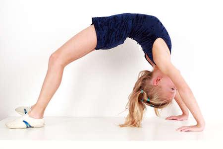 backward: Girl child performing backward bend gymnastics on white background Stock Photo