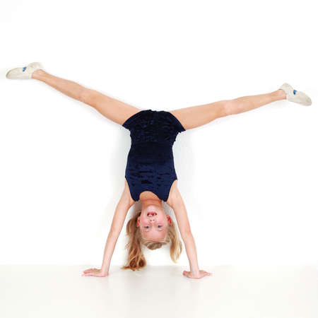 female gymnast: Girl child performing gymnastic balance training on white background