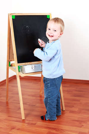 Adorable boy playing with chalkboard photo