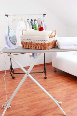 ironing board: Basket with laundry and ironing board
