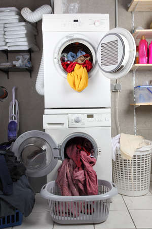 Baskets of dirty laundry in the washing room with dryer and washing machine photo