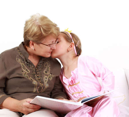 Cute little girl reading with grandmother and giving a kiss photo