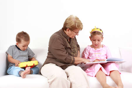 Grandma helping gorl by reading and playing with baby photo