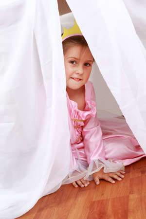 Adorable girl dressed as princess playing hide-and-seek at home