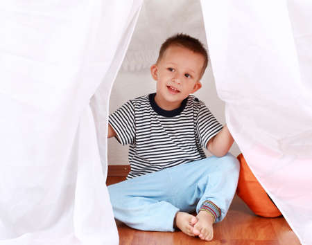 Adorable boy playing hide-and-seek at home photo