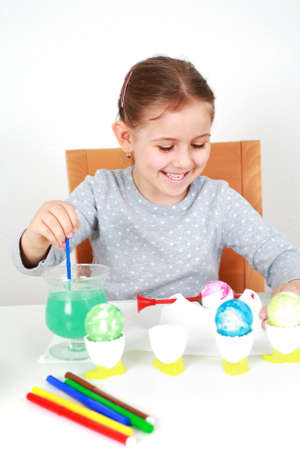 Cute little girl painting Easter eggs Stock Photo - 9044984
