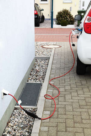 Detail of electric car charging battery from house wall jack photo