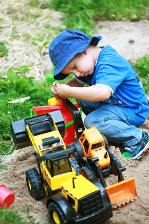 Cute boy playing with digger at the playground photo